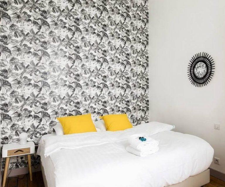 Vue d'une chambre avec un papier peint végétal noir et blanc