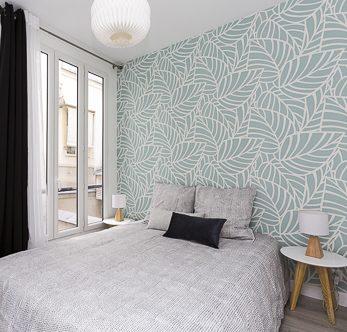 Photo d'une chambre avec un papier peint bleu à feuillages