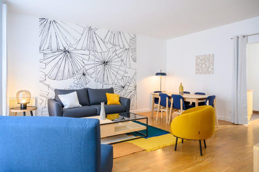 Vue d'un salon coloré avec un papier peint à palmiers par Liza Lena
