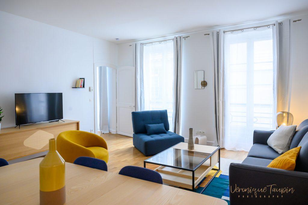 Une vue d'un salon avec du mobilier bleu et jeune