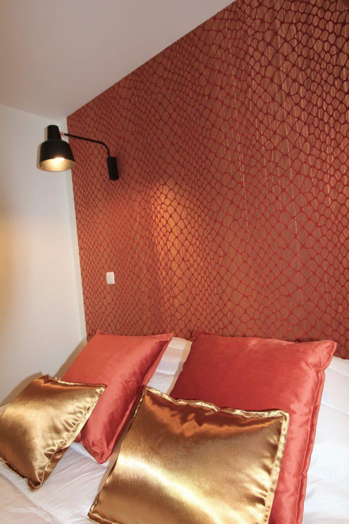 tête de lit avec un papier peint cuivré