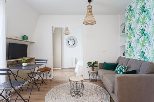 Vue d'un salon et une chambre avec un papier peint tropical