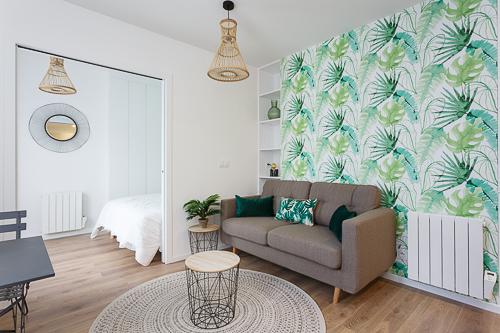 Vue d'un salon avec un papier peint à feuillage tropical