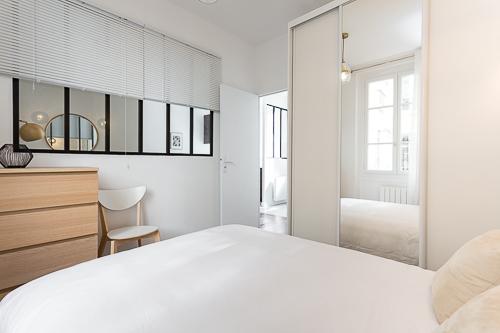 Chambre avec une vue sur le salon par une verrière