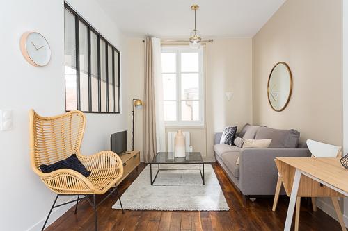 salon avec une verrière sur la chambre et fauteuil en rotin