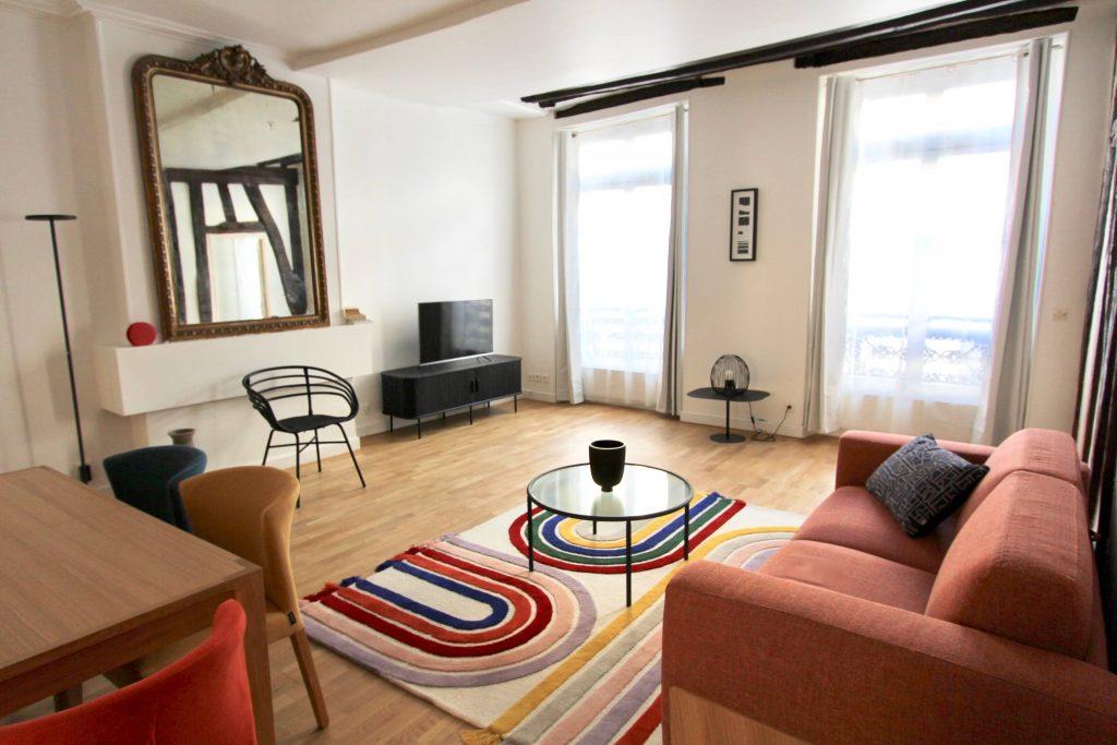 photo d'un salon avec cheminée poutres et mobilier coloré