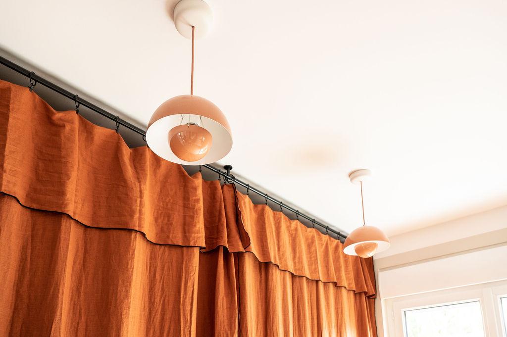 Gros plan sur des rideaux terracotta en lin et des luminaires assortis