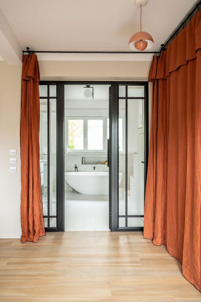Vue d'une chambre parentale vers la salle de bain séparée par une verriere noire