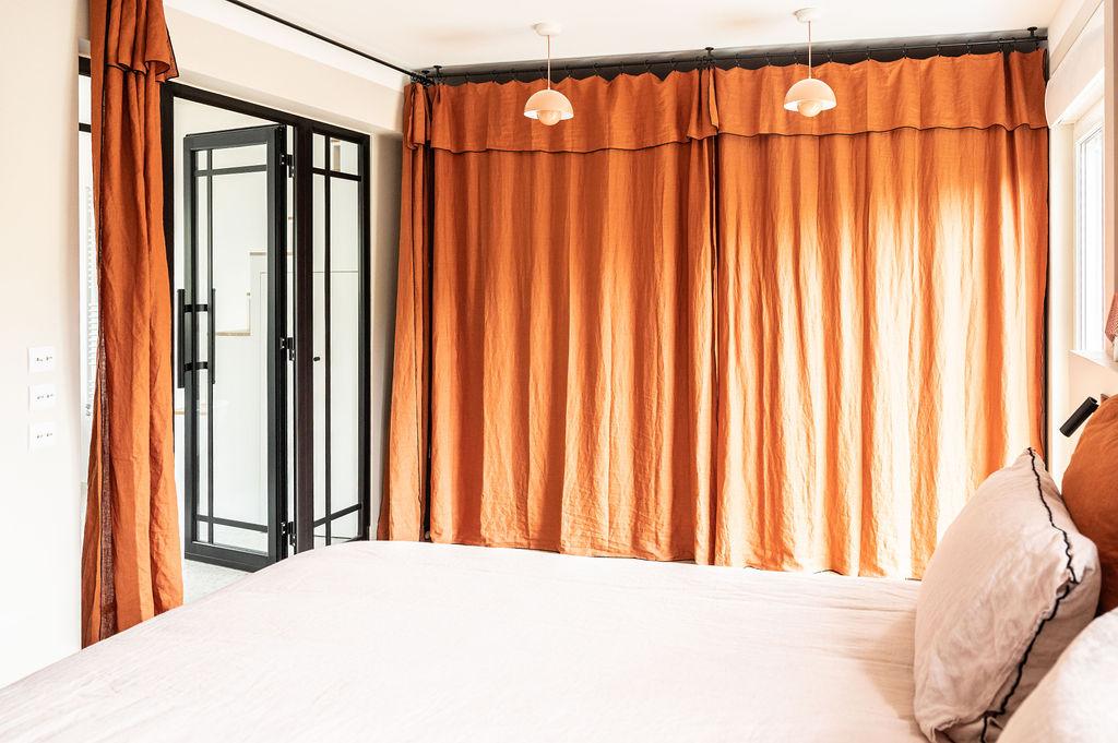 Photo d'une chambre redécorée avec des rideaux terracotta pour fermer le dressin