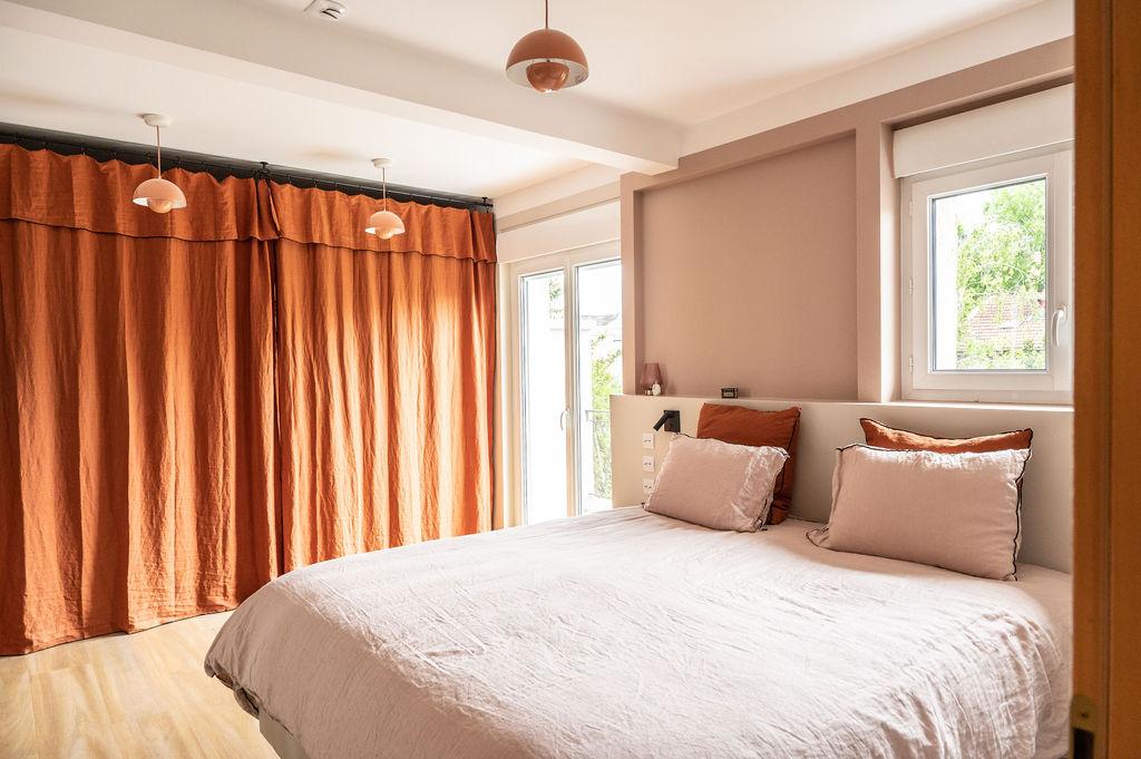Photo d'une chambre redecoree par Liza Lena avec un lit rose pooudé et des rideaux en lin terracotta