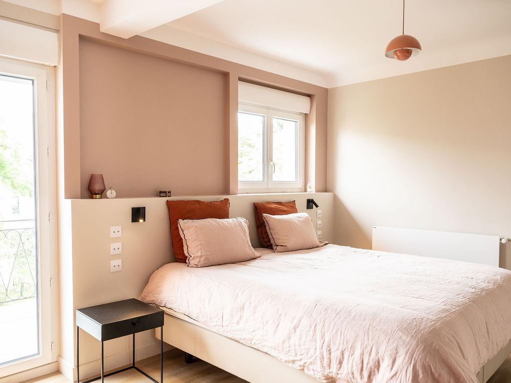Photo d'une chambre avec une niche en tete de lit et du linge de lit en lin